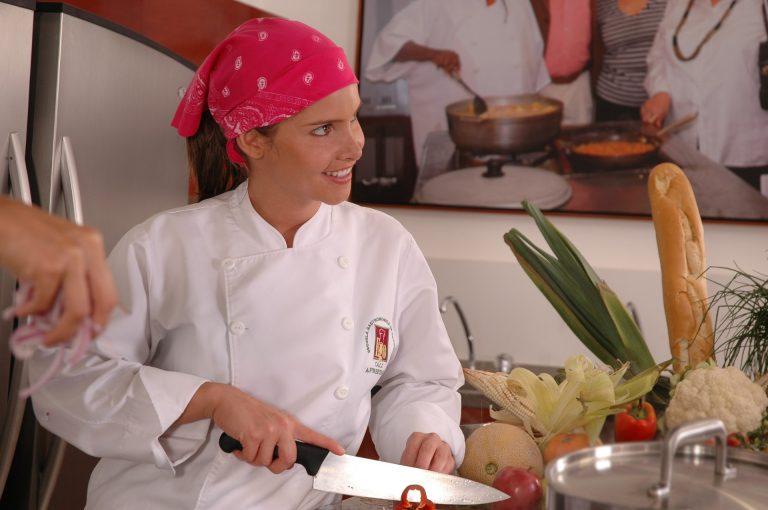 Körperhygiene, Frau mit rotem Kopftuch und weißer Kochjacke schneidet in einer Küche mit einem Messer eine rote Paprika.