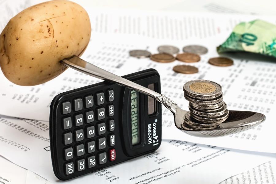 Kostenstellenrechnung, Kartoffel an einem Löffel auf einem Taschenrechner balanciert.