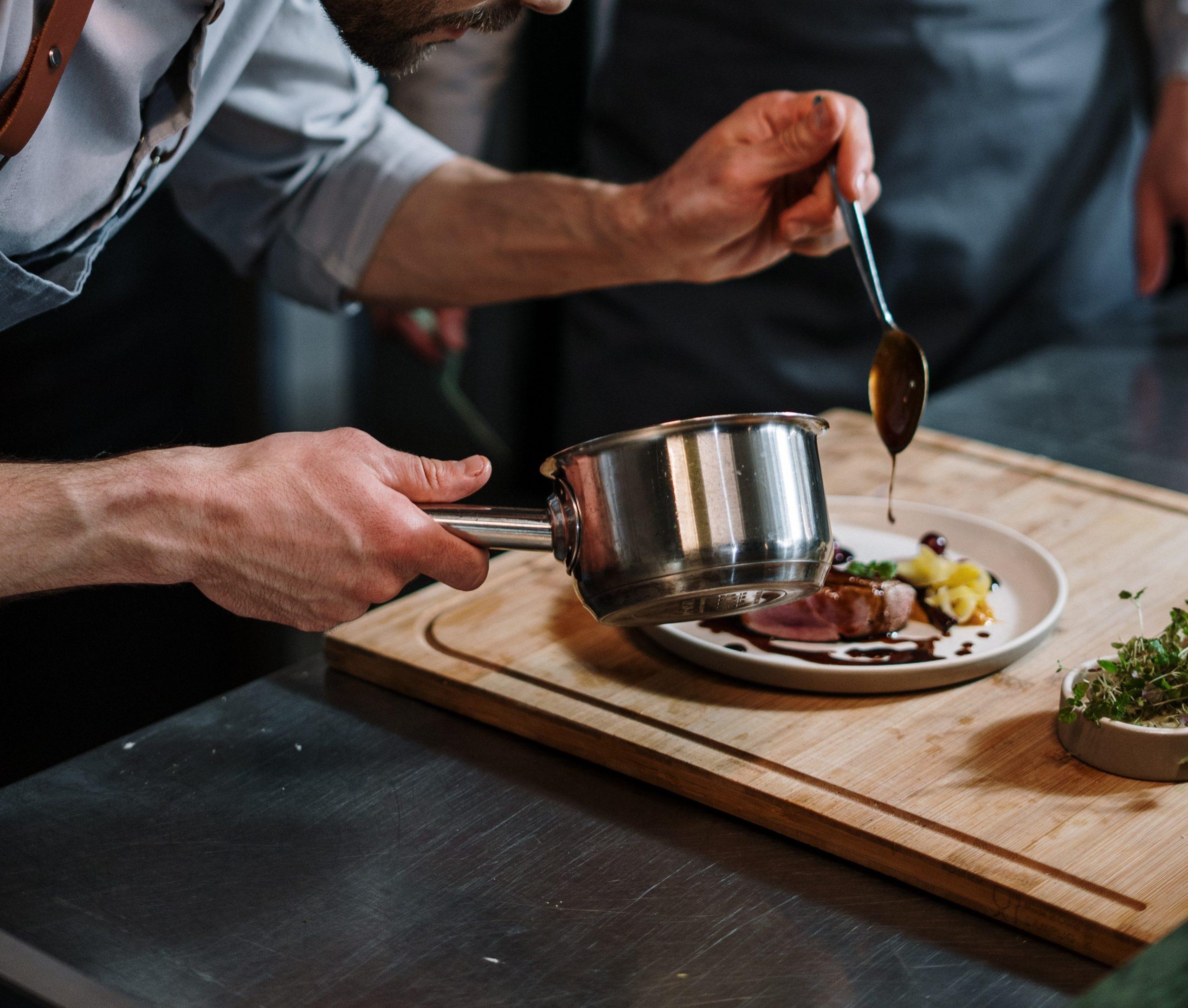 Gastronomieberatung, Koch richtet Teller in einer Küche an.
