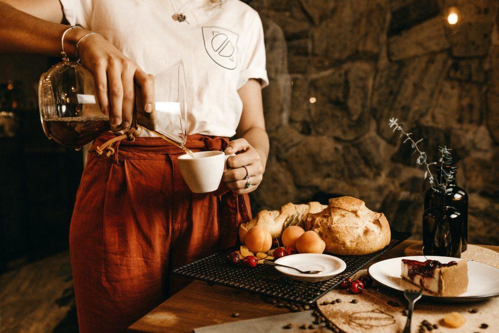 Fachkräftemangel nach Corona in der Gastronomie und Hotellerie. Frau gießt einen Kaffee in eine Tasse ein. Vor ihr steht ein Tisch. Auf einem Teller ist ein Kuchen.