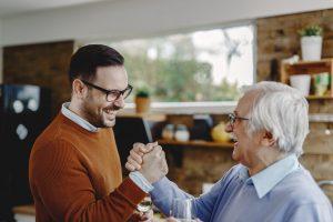 Nachfolgeregelung. Unternehmensnachfolge. Vater und Sohn geben sich die Hand.